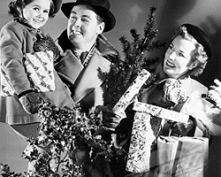 Family carrying Christmas decorations and parcels, 1940s.